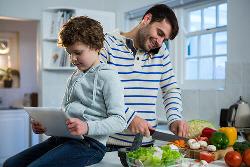 Father talking on mobile phone while chopping vegetables and son using digital tablet in the kitchen