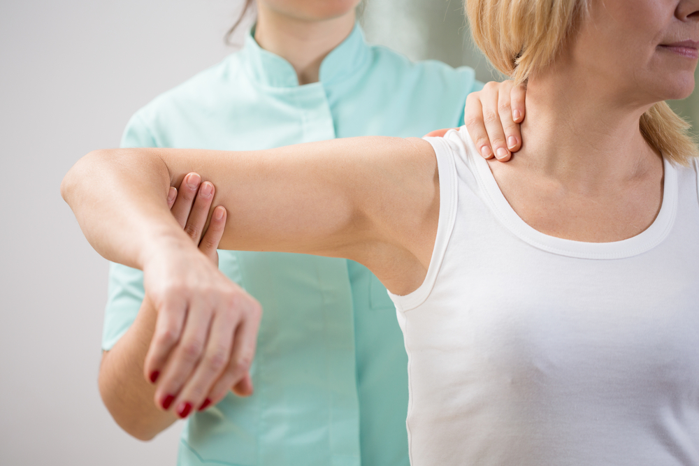 Physical therapist diagnosing patient with painful arm-1